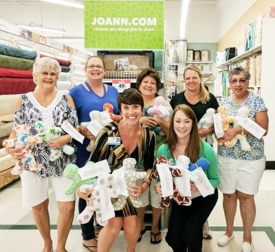 Members of the Jo-Ann Fabric and Craft Stores with donated Me Dolls